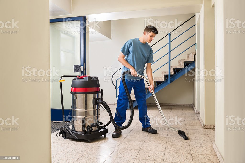 Male Worker Cleaning With Vacuum Cleaner stock photo