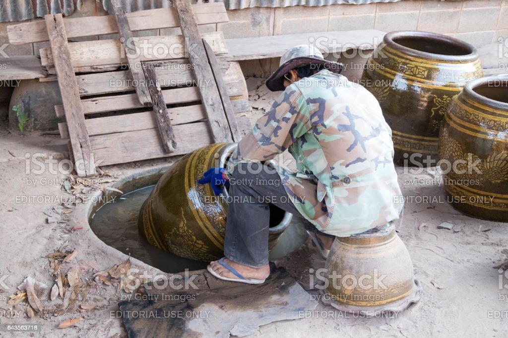 Male worker float Dragon jar on the water to find small defects or very little holes on jars. stock photo