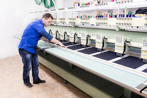 male worker how set automatic embroidery machine in textile factory - embroidery machine stock pictures, royalty-free photos & images