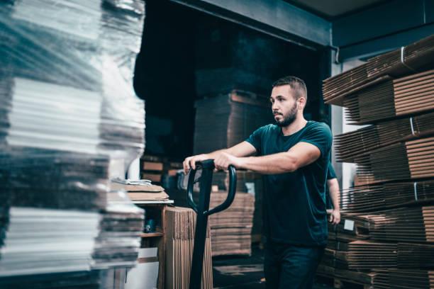 hombre trabajador en fábrica de cartón empujar palets en carro de transporte - trabajar hasta tarde fotografías e imágenes de stock