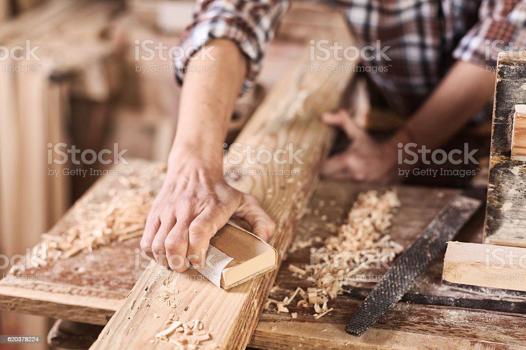 Male worker in carpenter workshop using sandpaper foto de stock royalty-free