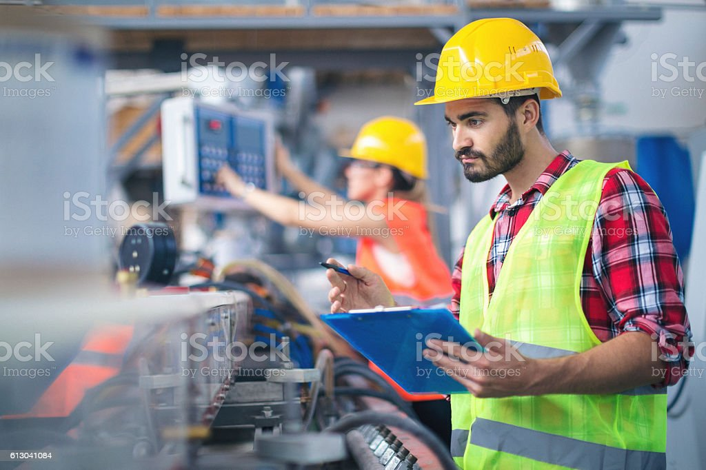 Male worker in factory taking notes stock photo