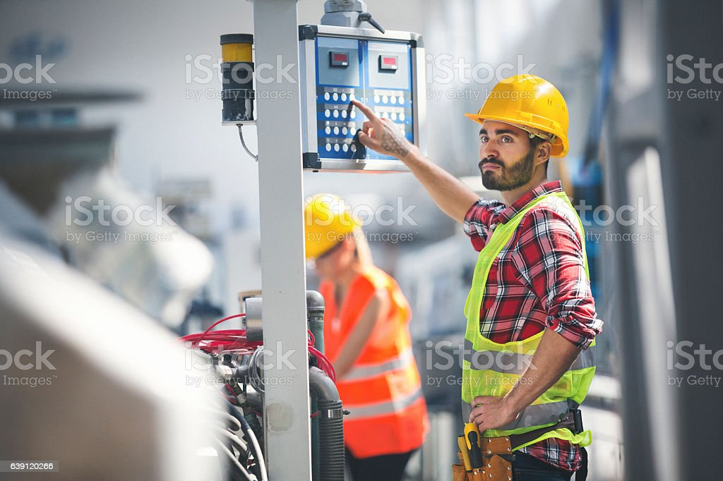 Male worker in factory using control panel stock photo