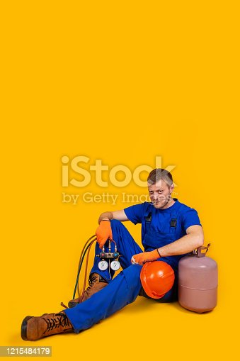 A male worker in overalls sits on the floor with a suppressed feeling of unemployment, problems of the economy from the economic downturn. The concept of the economic crisis, unemployment