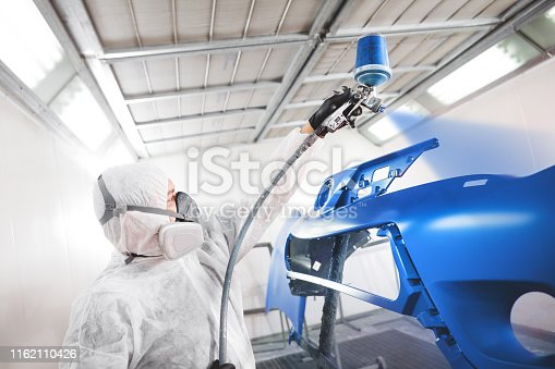 Male worker in protective clothes and mask painting car bumper using spray paint. Body repair of the vehicle after the accident.