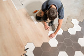 istock Male worker installing new wooden laminate flooring. The combination of wood panels of laminate and ceramic tiles in the form of honeycomb. Kitchen renovation. 1060784680