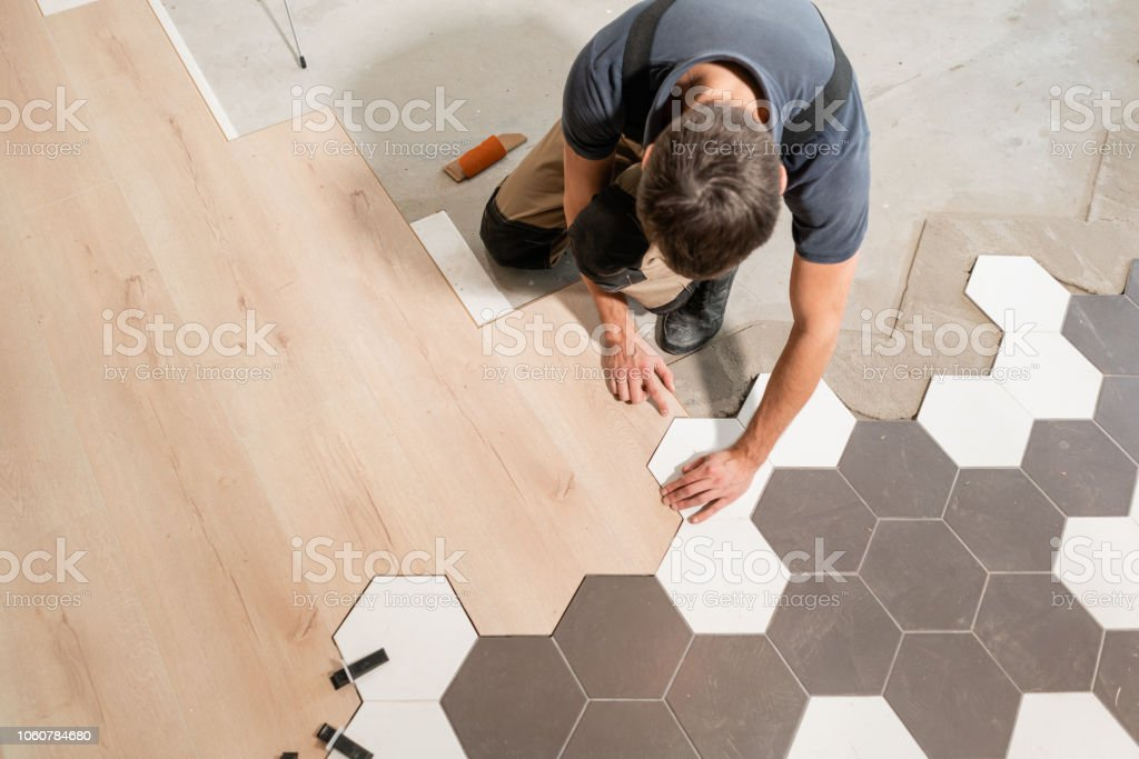 Männliche Arbeiter installieren neue hölzerne lamellenförmig angeordneter Bodenbelag. Die Kombination aus Holzplatten von Laminat und keramische Fliesen in Wabenform. Küche renoviert. – Foto