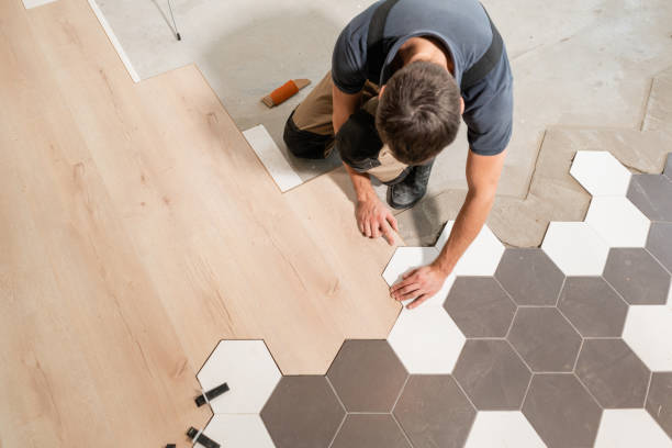 male worker installing new wooden laminate flooring. the combination of wood panels of laminate and ceramic tiles in the form of honeycomb. kitchen renovation. - materiał budowlany zdjęcia i obrazy z banku zdjęć
