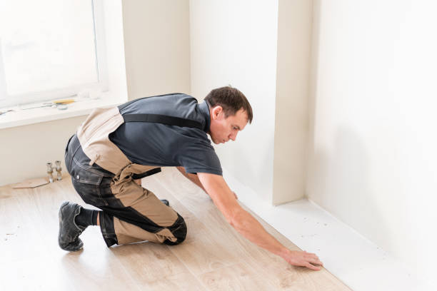 Male worker installing new wooden laminate flooring. The combination of wood panels of laminate and ceramic tiles in the form of honeycomb. Kitchen renovation stock photo
