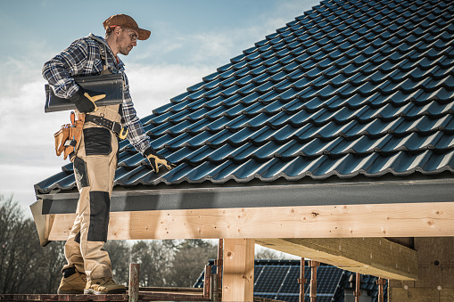 Male Caucasian Roofer Installing  Roofing Tiles On Newly Built Home.