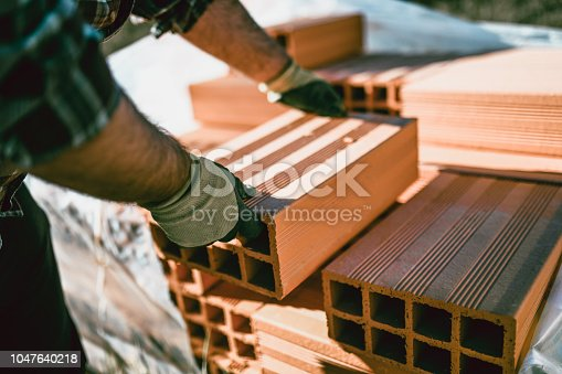 Male Worker With Protective Gloves Is Passing Clay Hollow Brick