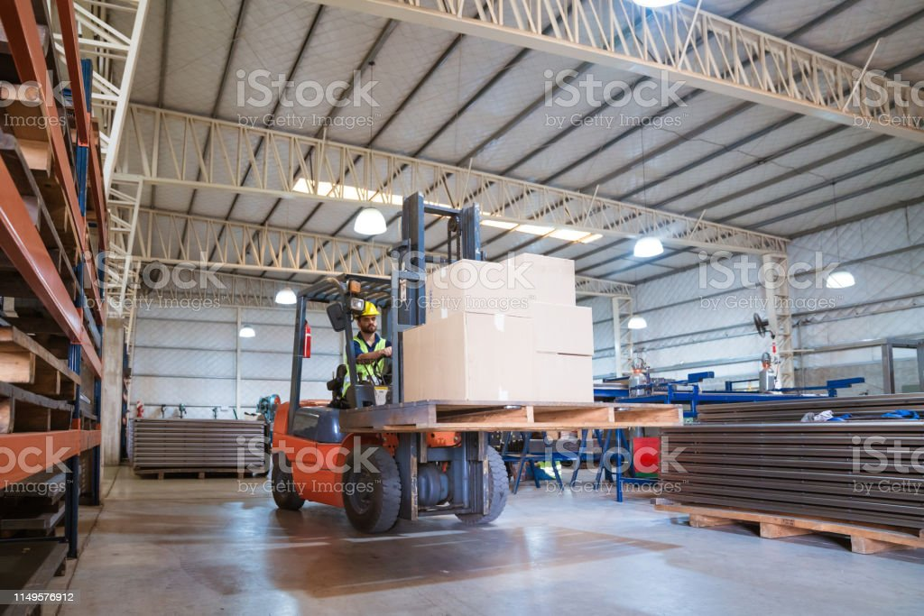 Male worker moving cardboard boxes using forklift Warehouse male worker moving cardboard boxes. Engineer is working in manufacturing industry. He is driving forklift. 20-24 Years Stock Photo