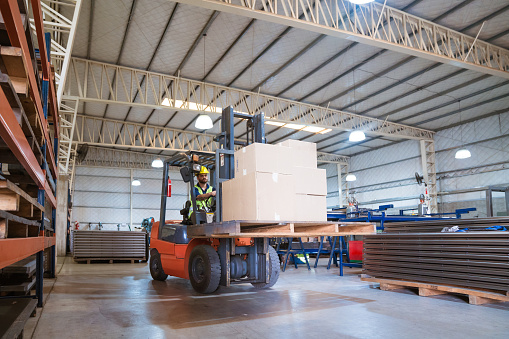 Male Worker Moving Cardboard Boxes Using Forklift Stock Photo - Download Image Now
