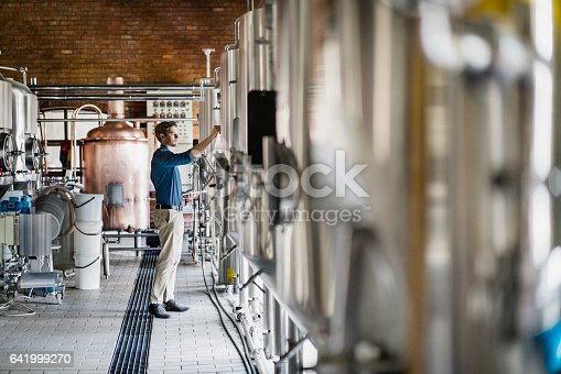 Male worker operating machinery in brewery. Full length of professional is holding digital tablet while working amidst metallic vats. He is in beer industry.