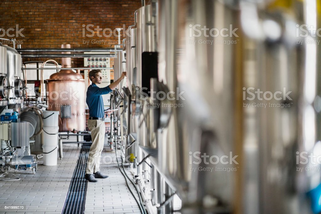 Male worker operating machinery in brewery – zdjęcie