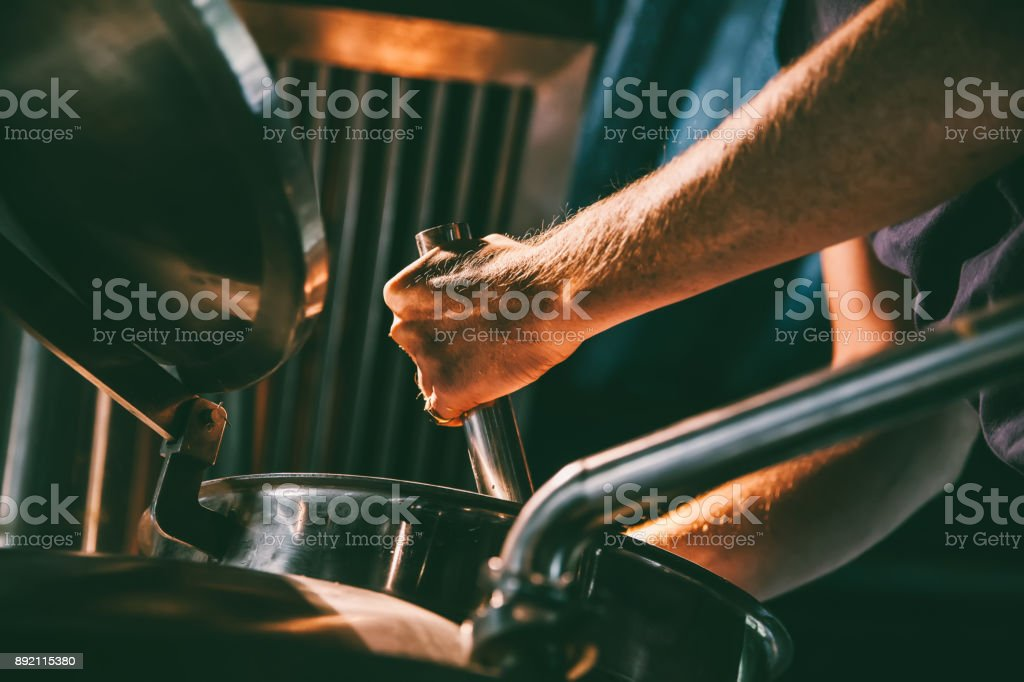 Male worker operating machinery in brewery stock photo