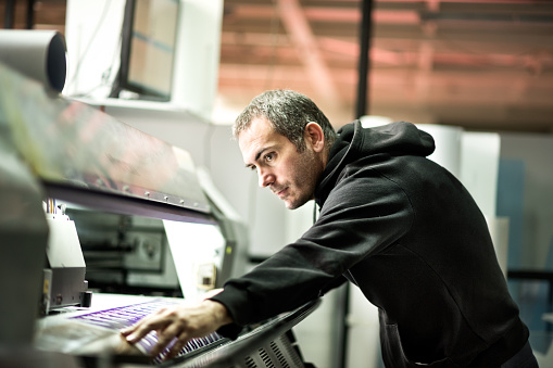 Skilled worker operating on industrial printer inside the printing factory.