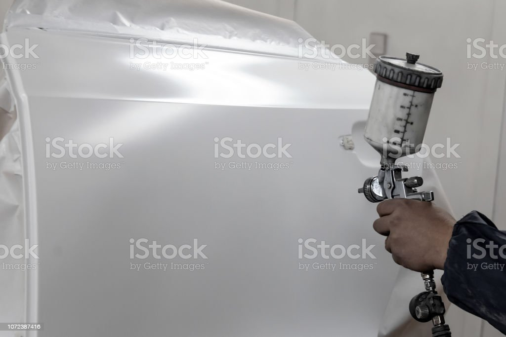 A male worker paints with a spray gun a part of the car body in white after being damaged during an accident. Door from the vehicle during the repair in the workshop. stock photo