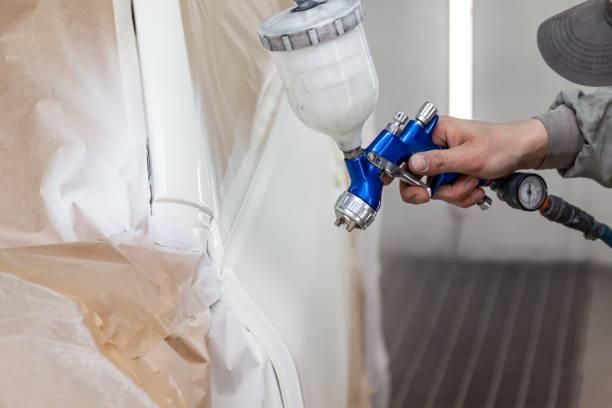 一名男性工人在一次事故中受損, 用噴槍用白色油漆汽車車身的一部分。在車間維修過程中, 車輛的門。汽車服務業專業圖像檔