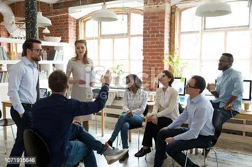 987123762 istock photo Male worker raise hand asking question at office teambuilding 1071915646