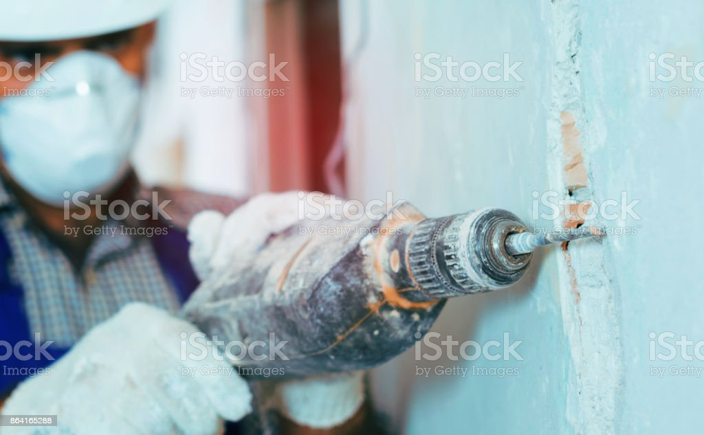 Male worker repairing with drill in mask royalty-free stock photo