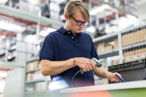 Male worker scanning package for delivery stock photo