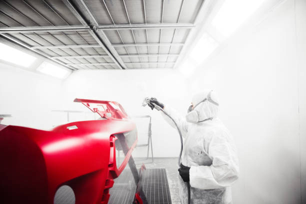 Male worker sprays varnish with spray gun on car bumper after painting. Male worker sprays varnish with spray gun on car bumper after painting. Auto repair garage. lacquered stock pictures, royalty-free photos & images