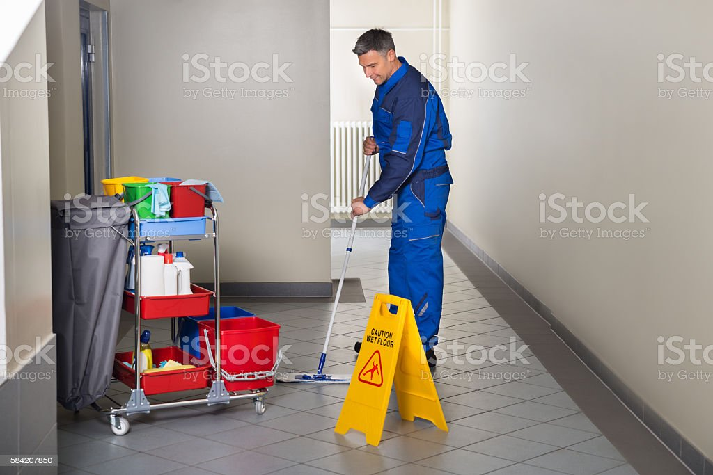 Male Worker With Broom Cleaning Corridor stock photo