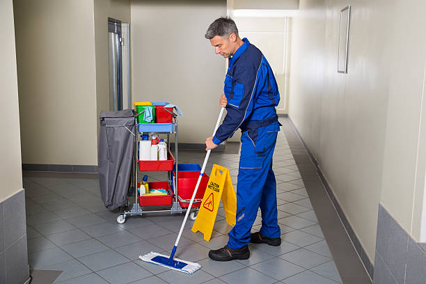 male worker with broom cleaning corridor - custodian stock pictures, royalty-free photos & images