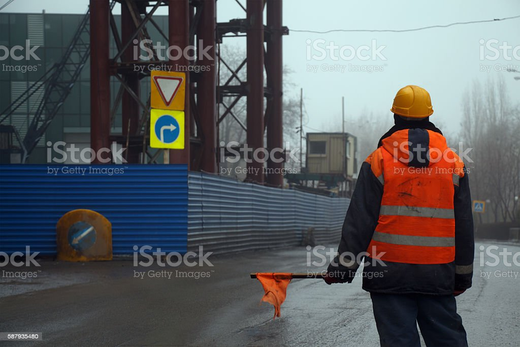 Male worker with flag standing across the road preventing traffic stock photo