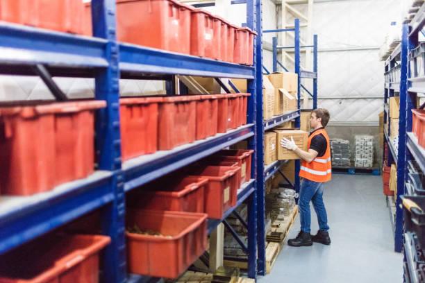 männliche arbeitnehmer arbeiten im lager firma - kreativer speicher stock-fotos und bilder