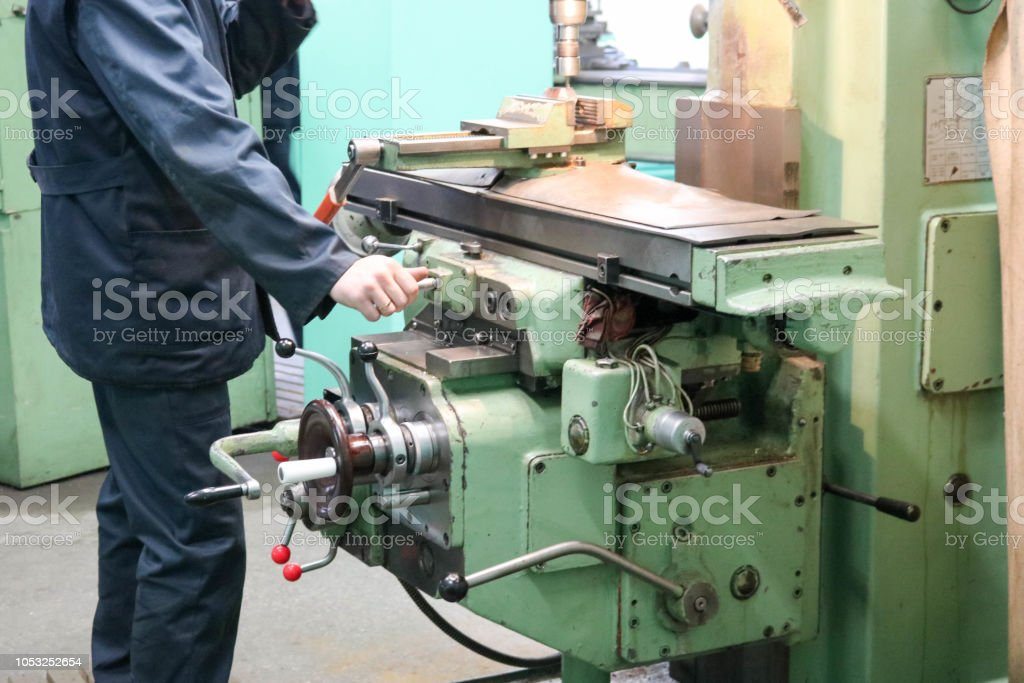 A male worker works on a larger metal iron locksmith lathe, equipment...