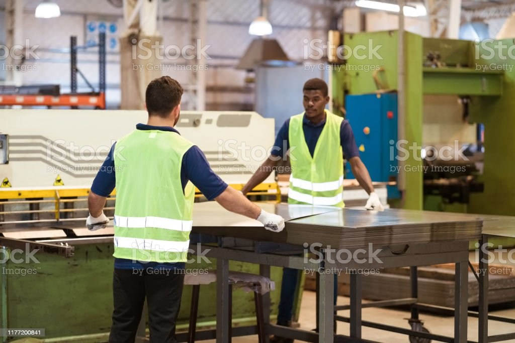 Male workers adjusting metallic sheet in machinery Male engineers adjusting metallic sheet on machinery. Young workers are in protective workwear at factory. They are into manufacturing occupation. 20-24 Years Stock Photo