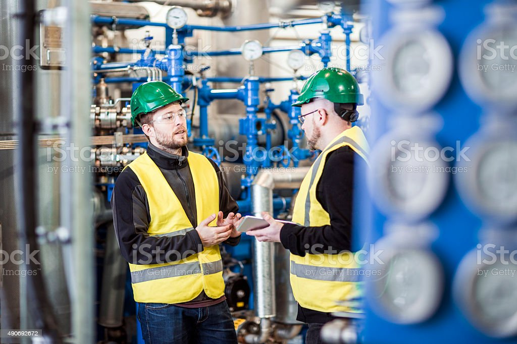 Male workers discussing in industry stock photo