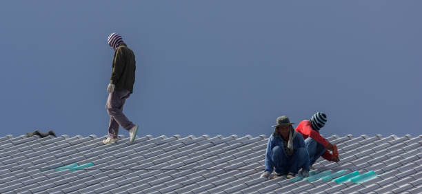 Male workers install tiled roofs stock photo
