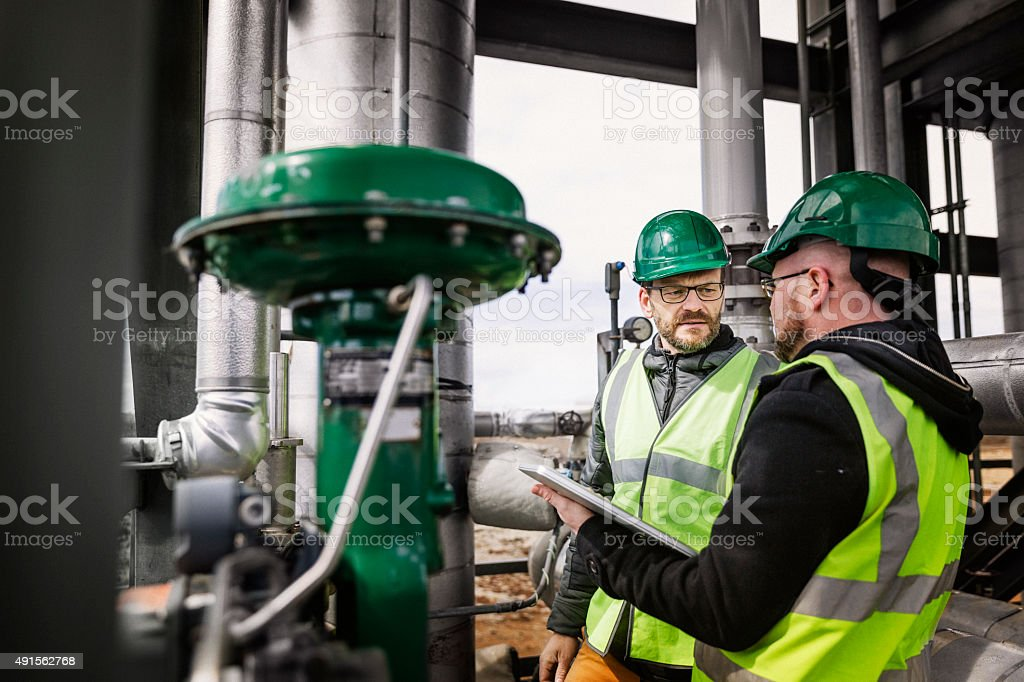 Male workers standing and discussing at factory stock photo