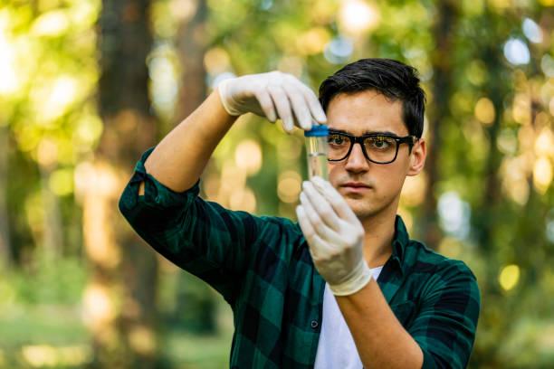 Fonctionnement masculin contrôlant la qualité de l'eau avec le tube en verre. Jeune homme d'écologiste dans la forêt - Photo