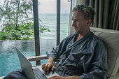 Young man working from home, private pool villa overlooking the ocean, Thailand. People working remotely and luxury lifestyle concept. Caucasian male using laptop, bathrobe, hotel room.