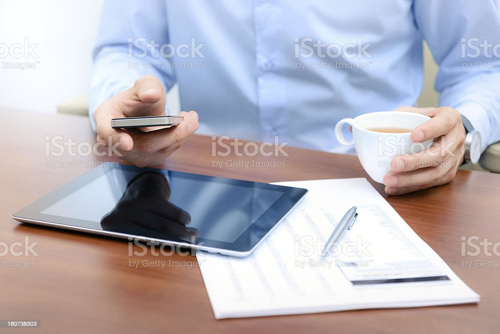 Male working on a mobile phone and having a coffee  royalty-free stock photo