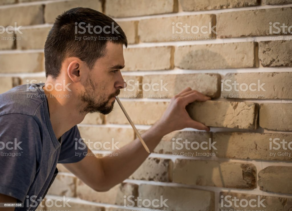 male works with brick wall with centimeter royalty-free stock photo