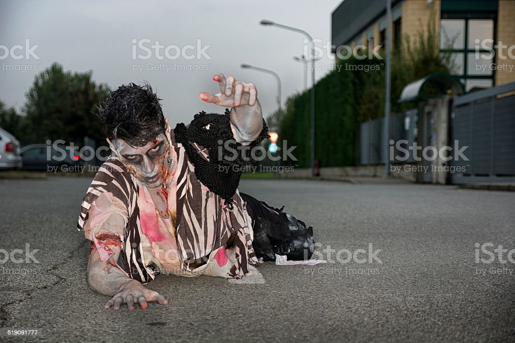Male zombie crawling on his knees, on empty city street stock photo