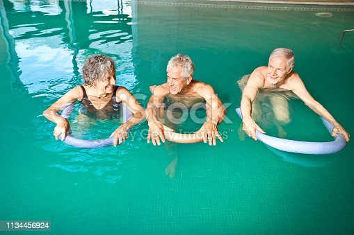 1047537292istockphoto Males and female swimming with noodle floats 1134456924