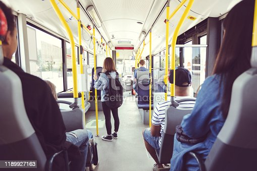 Men and women traveling in public transport. Teenage girl is standing at aisle while commuting by bus. They are in vehicle.