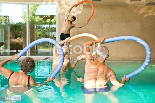 1047537292istockphoto Males and females exercising in swimming pool 1134457716