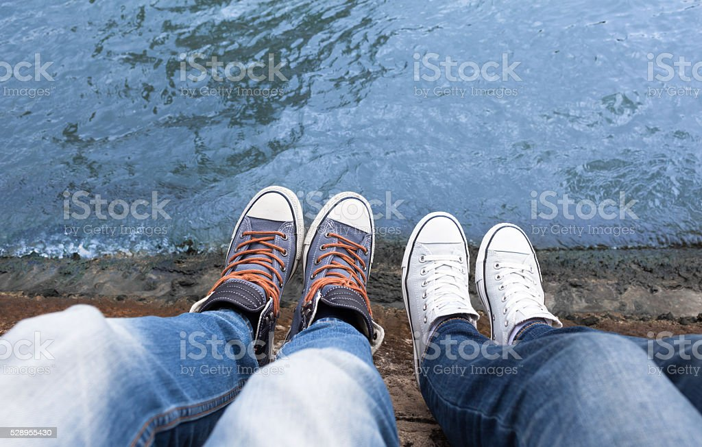 Male's and female's feet relaxing by the river stock photo