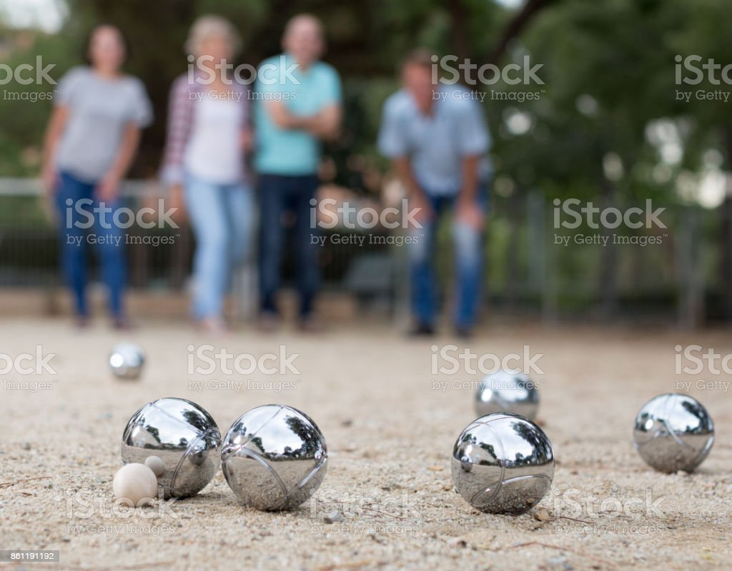 Males and females playing petanque stock photo