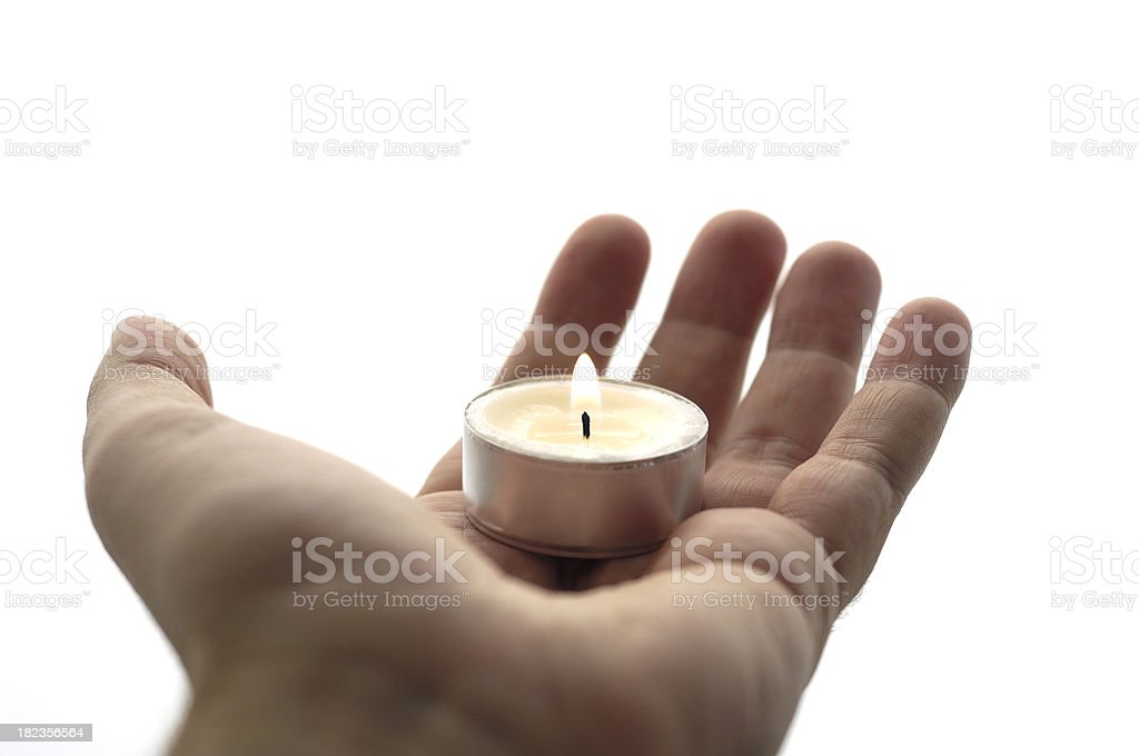 Male's hand offering a burning candle royalty-free stock photo