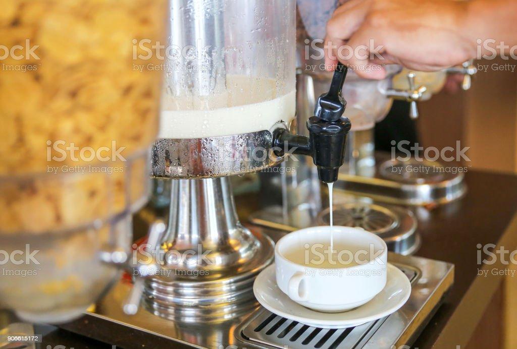 Males hand pressing milk dispenser stock photo