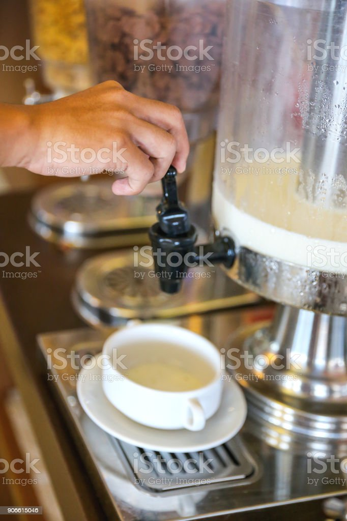 Males hand pushing faucet on milk dispenser stock photo