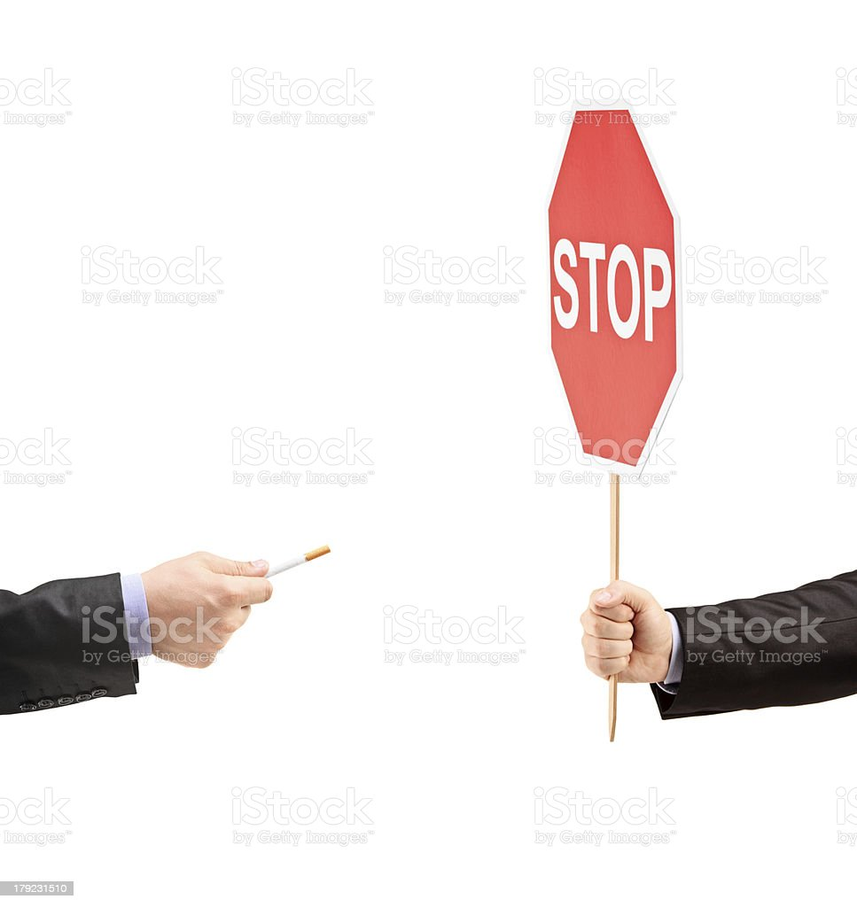Male's hands holding a stop sign and refusing cigarette royalty-free stock photo